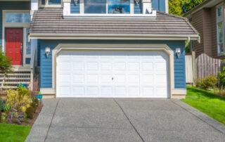 blue home with a white vinyl garage door